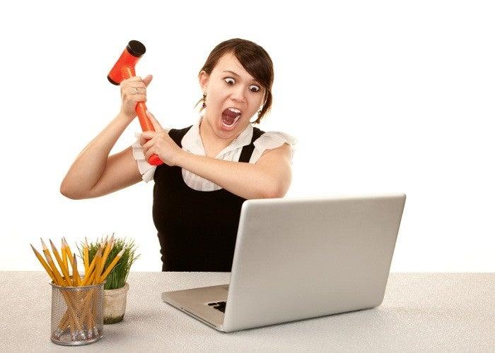 Trabalhador de escritório muito feminino, destruindo o computador portátil